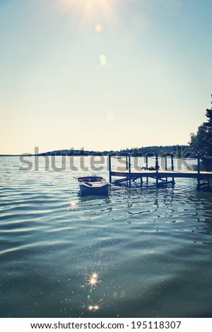 Boat on the lake by the dock in summer - instagram effect - stock photo