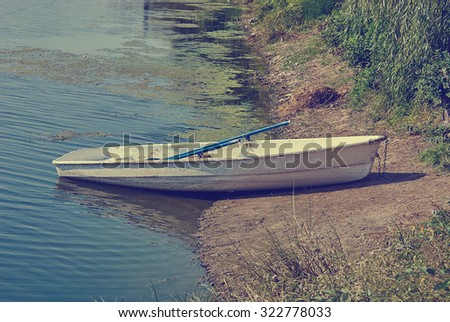 Boat on the lake, pond. Water tina. Retro toned image. - stock photo