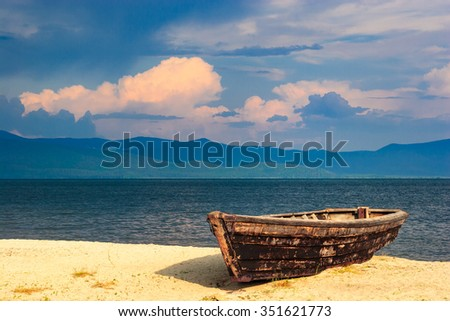 boat on the sandy shore of Lake Baikal - stock photo