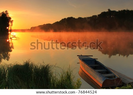 Boat on the shore of a misty lake on a summer morning - stock photo