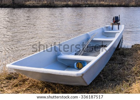 Boat on the shore of a mountain river. National Nanai boat on the shore of a mountain river. - stock photo