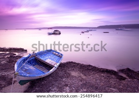 boat over land at seaside taken with long exposure in Canakkale / Turkey at sunset with a colorful sky  - stock photo