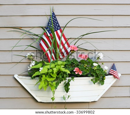 boat planter with flowers and american flags - stock photo