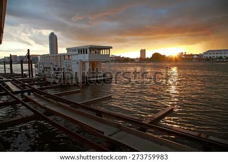 Boat restaurant at Chao phraya river against sunset in Bangkok, Thailand - stock photo
