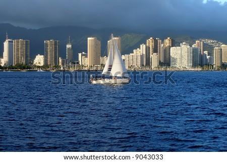 Boat sailing along Honolulu skyscrapers in Hawaii - stock photo