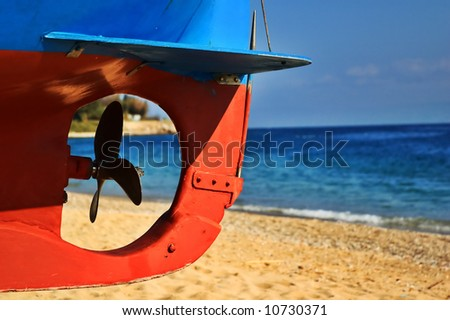 Boat screw with beach and sea in the background - stock photo