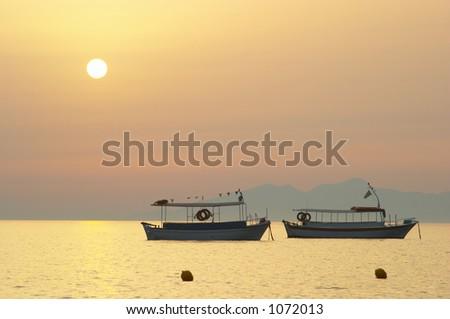 Boat silhouette at sunrise  2 - stock photo