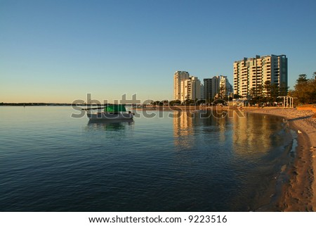Boat sits in a quiet bay by the buildings on the shore at sunrise. - stock photo