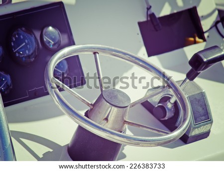 boat steering wheel and throttle on a sunny day. iso 100, processed for vintage effect. - stock photo