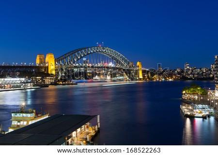 Boat traffic around Sydney harbour Bridge at rush hour on a winter's evening in Sydney, Australia - stock photo