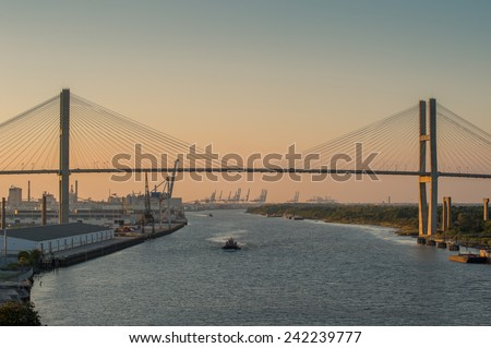 Boat traffic at dusk on Savannah River below the Eugene Talmadge Memorial Bridge. Established in 1733 Savannah is the oldest town in Georgia. - stock photo