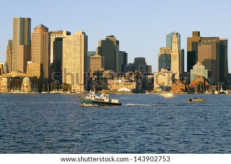 Boat travels in front of Boston Harbor and the Boston skyline at sunrise as seen from South Boston, Massachusetts, New England - stock photo