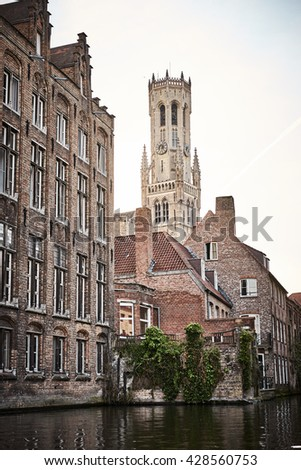 Boat trip on Canal in Bruges - Belgium / Facades and Belfry at Canal of Bruges in Belgium / Beautiful old Town of Bruges in Belgium - stock photo