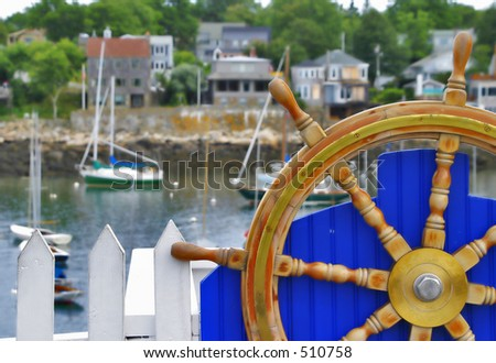 Boat Wheel on a blue fence with boats in the background - stock photo