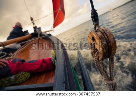 Boat with red sail in the sea. Detail. - stock photo