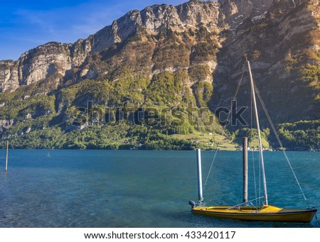 Boat with sails anchored on Walensee lake - Image taken in the Murg village, Switzerland, presenting a small boat on the Walensee lake in the morning sunlight, surrounded by the Swiss Alps mountains. - stock photo