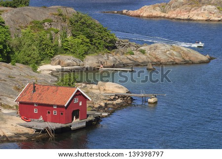 Boathouse and a boat on the rocky coast - stock photo