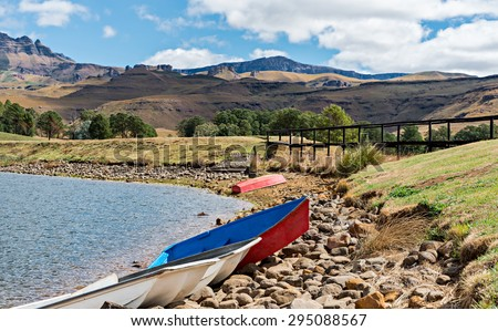 Boats and footbridge on lake shore with the Drakensberg mountains in the distance. Shallow depth of field with focus on boats in the foreground - stock photo