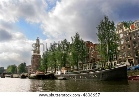 Boats and old historical houses along the Amstel river (city canal) in Amsterdam, Netherlands (Holland). - stock photo