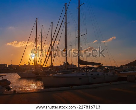 Boats and yachts in the harbor at sunset - stock photo