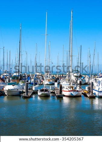 Boats and yachts on a pier in the summer sunny day - stock photo