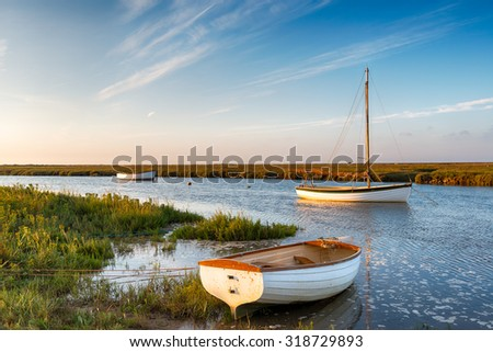 Boats at high tide on salt marshes at Blakeney on the north Norfolk coast - stock photo