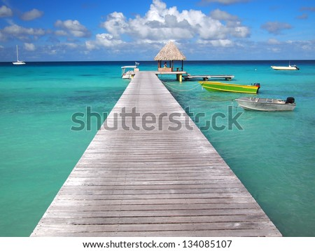 Boats attached to a pier and a thatched hut inside the tropical lagoon of the pacific atoll Rangiroa, an island of the Tahiti archipelago French Polynesia. - stock photo