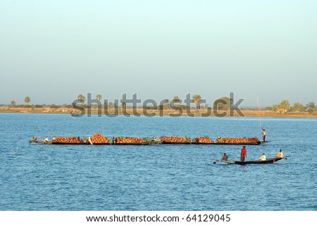 Boats carrying goods and people across river in West Africa - stock photo