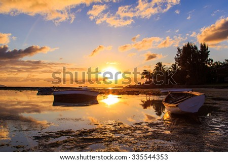 Boats docked during beautiful sunset / sunrise by the coasts of the island - stock photo