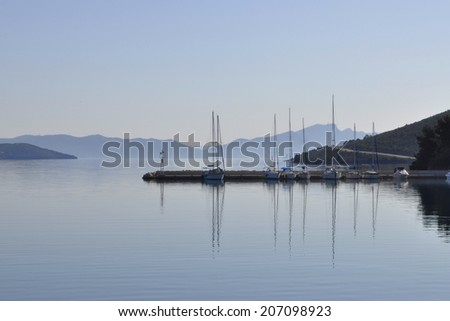 boats in a port and mountains in the distance - stock photo