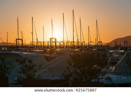 boats in Alghero harbor at sunset - stock photo