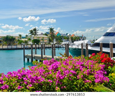 Boats line a tropical Caribbean waterway surrounded by colorful flowers - stock photo