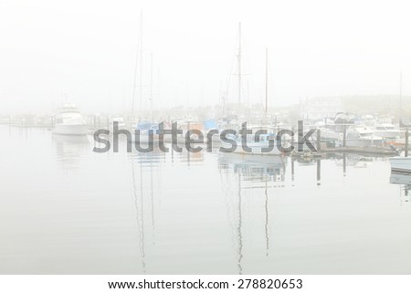 Boats moored during a dense fog in the marina at Newport, Oregon.   - stock photo