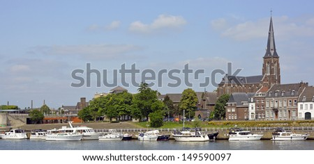 Boats moored on the River Meuse with part of the town of Maastricht beyond - stock photo