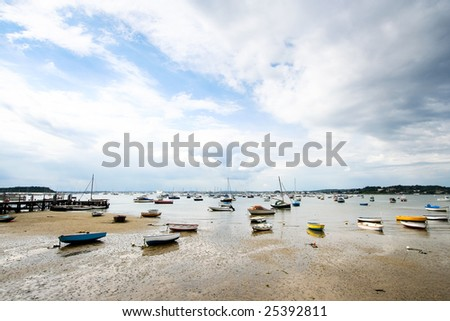 boats on low tide shore - stock photo