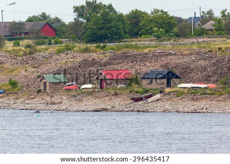 Boats on the beach by the boathouses - stock photo