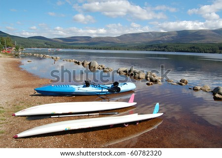 boats on the shore of loch morlich in the highlands of scotland - stock photo