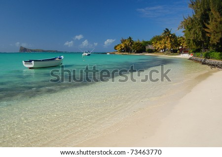 Boats on turquoise water of tropical sandy beach of Mauritius Island - stock photo