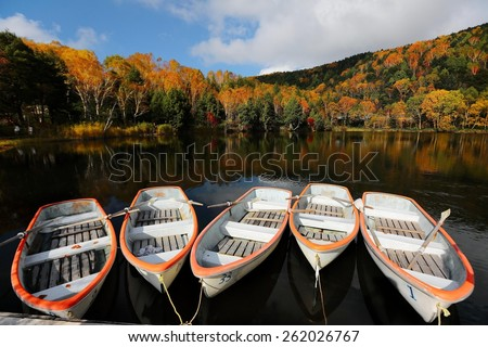 Boats parking on Lake Kido surrounded by autumn forests of vibrant colors ~ scenery of Kido Ike, Shigakogen  Japan  - stock photo