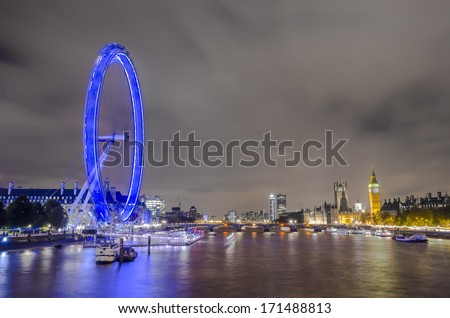 Boats passing along Thames river with night London skyline of Eye, Big Ben, House of Parlament over Westminiister bridge - stock photo