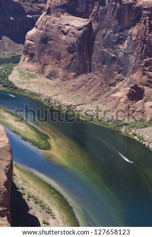 boats race down a canyon on the Colorado river near page arizona - stock photo