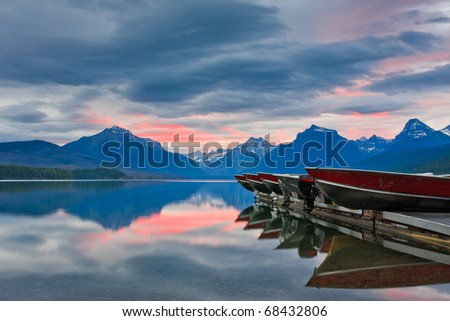 Boats rest on a dock during a colorful sunrise on a calm mountain lake, Montana. - stock photo