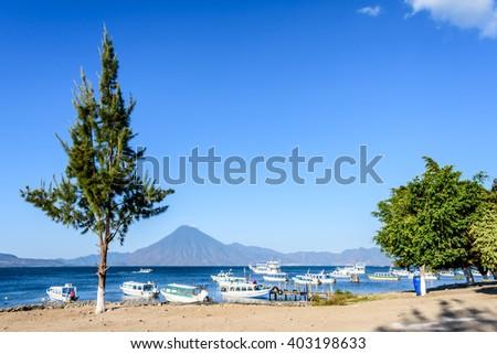 Boats & San Pedro volcano on Lake Atitlan in Guatemalan highlands - stock photo