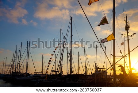 Boats with Morse flags at pier against dramatic sunset lighting (flare effect, sunset lighting) - stock photo