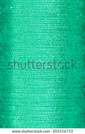 bobbin of green thread background texture macro - stock photo