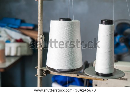 Bobbin of white thread on sewing machine in the factory - stock photo