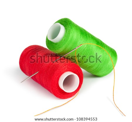 bobbins thread with needle and sewing pin isolated on white - stock photo