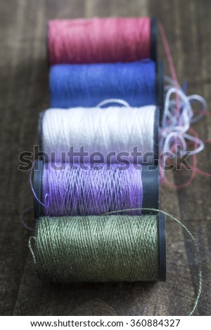 bobbins with thread on the table, close  up - stock photo