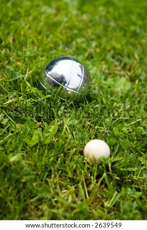 Bocce balls sitting in the green grass, close to the target. -shallow depth of field.- - stock photo