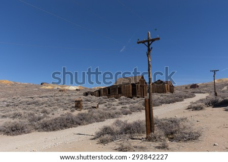 BODIE, CA, USA, MARCH, 2015: Power lines against the background of abandoned wooden buildings and gold mines in Bodie Ghost Town Historic State Park, California  - stock photo